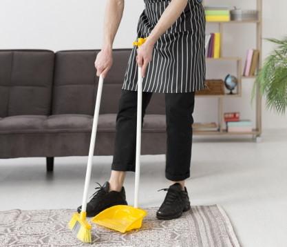Καθαρισμός χαλιού με σκούπα και φαράσι