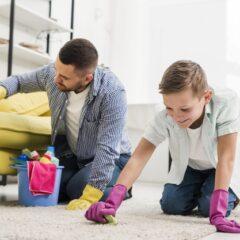 Άνδρας και παιδί καθαρίζουν χαλί και καναπέ με το χέρι