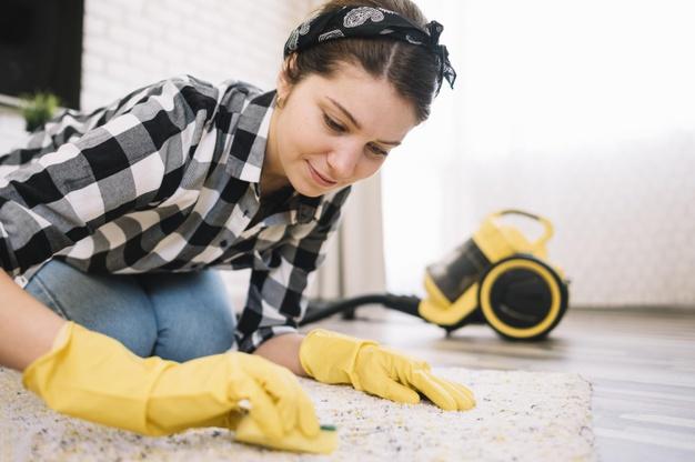 Γυναίκα καθαρίζει χαλί με το χέρι