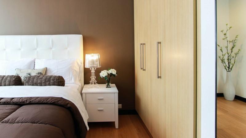 Καφέ ντουλάπα εντός υπνοδωματίου απέναντι από κρεβάτι