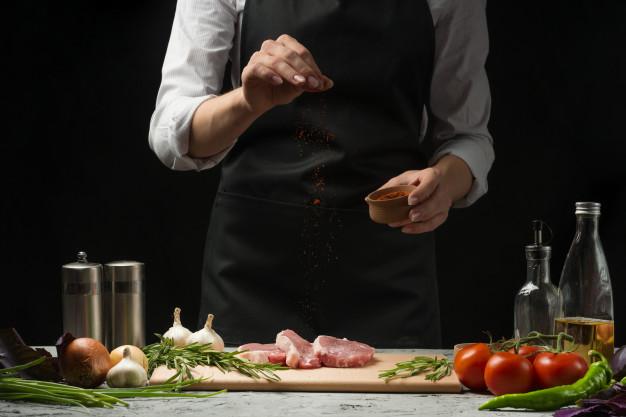 Ποδιά σεφ σε γυναίκα επάνω από ωμό κρέας