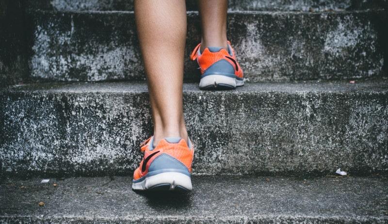 Άνδρας ανεβαίνει σκαλιά με αθλητικά παπούτσια